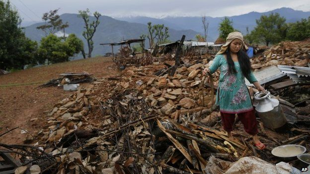 A woman recovers cooking pots from her collapsed home destroyed village of Paslang in Gorkha