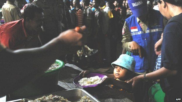 Mostly Rohingya migrant women and children are served a ration by government social welfare personnel in Aceh province, Indonesia (14 May 2015)