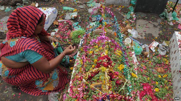 An Indian woman from the Hindu Devipujak community burns incense on the grave of her dear departed as she observes 'Divaso', an annual memorial day for the departed souls, at a graveyard in Ahmedabad on July 26, 2014.