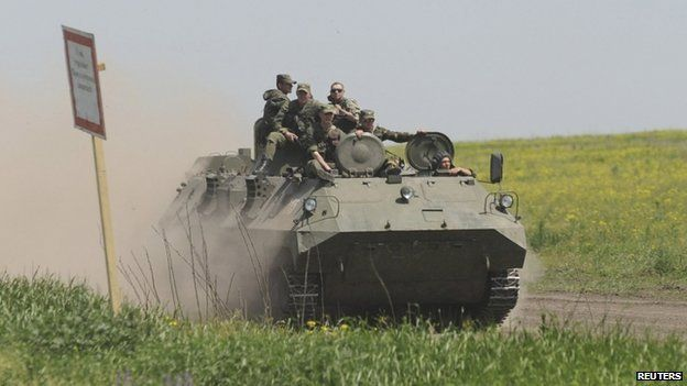 Men wearing military uniforms ride atop an armoured personnel carrier (APC) during exercises at the Kuzminsky military training ground near the Russian-Ukrainian border in Rostov region, Russia, 25 May 2015