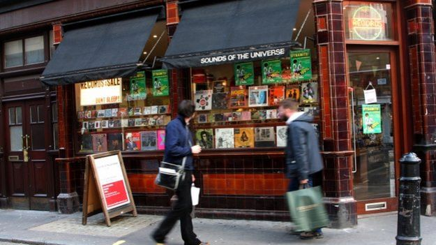 People walking past a record shop