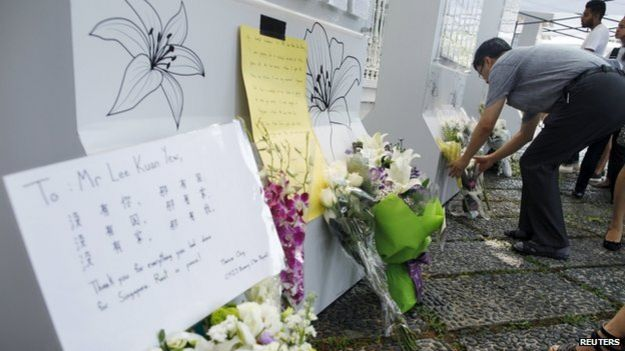 People lay flowers, as they mourn the passing of former prime minister Lee Kuan Yew, outside the Istana in Singapore, on 23 March 2015