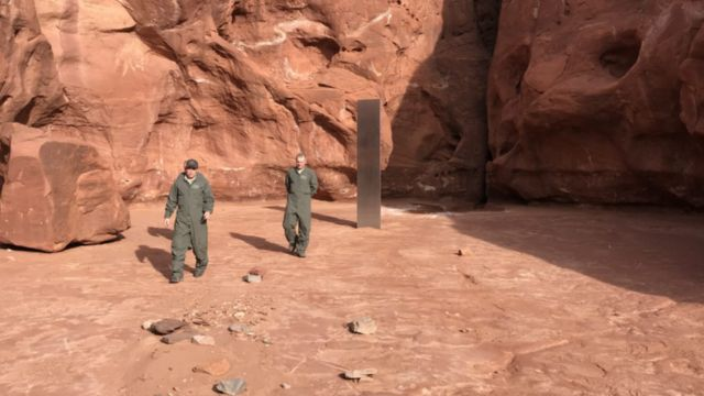 Wildlife officials walking away from the monolith