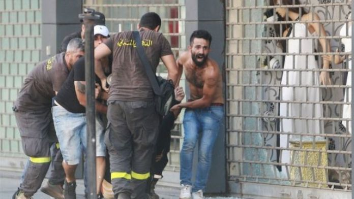 Armed men carry a wounded man