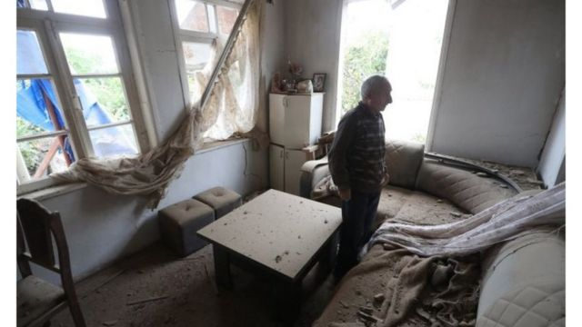 A man in his damaged home
