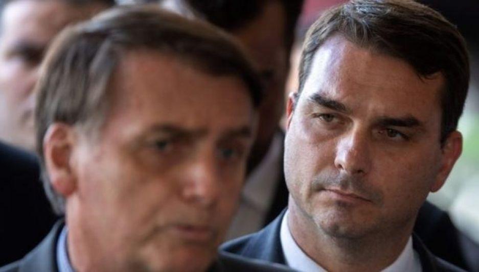 Bolsonaro dá entrevista, com Flávio Bolsonaro aparecendo atrás