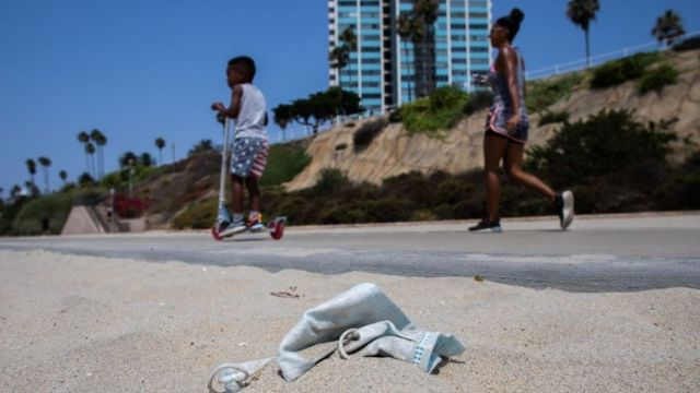 A woman and a child walk the promenade in Long Beach, California while a discarded face mask can be seen on the floor
