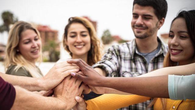 Grupo de mulheres e homens juntando as mãos