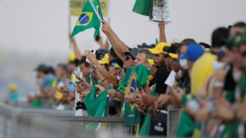 People in green, yellow and blue clothes behind a fence