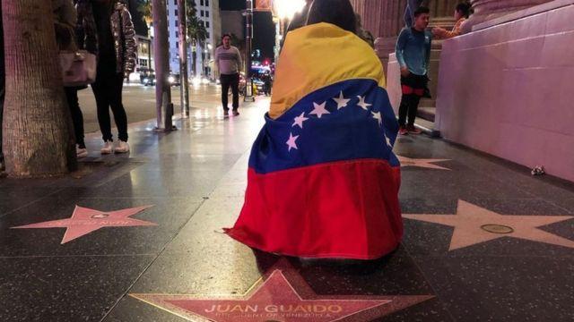 Una mujer está de rodillas y arropada con una bandera de Venezuela en el Paseo de la Fama de Hollywood.