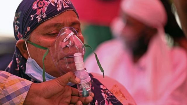 A woman tries to breathe with an oxygen tube