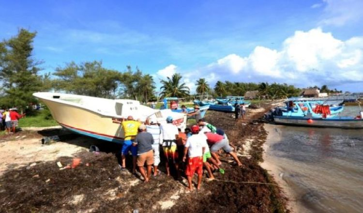pescadores sacan sus botes del agua en Cancún.