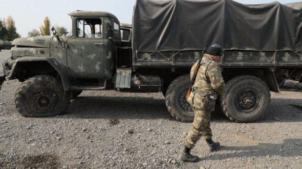 جندي أذربيجاني يمر بجوار مركبة عسكرية تم الاستيلاء عليها من القوات الأرمينية في ناغورنو كاراباخ خلال القتال قبل وقف إطلاق النار