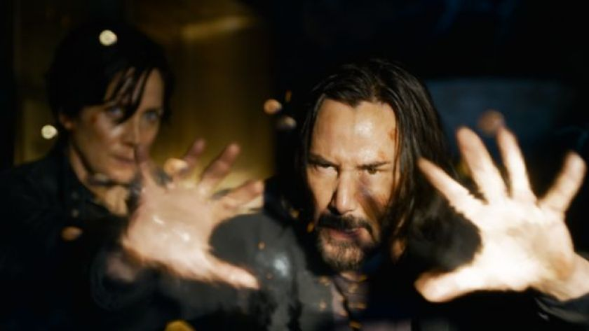 Keanu Reeves playing his character Neo alongside Carrie-Anne Moss's Trinity (left)
