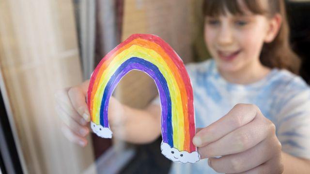 Garota branca de franjinha segura um arco-iris de papel