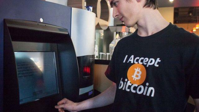 """رجل يرتدي قميصاً كتب عليه """"اقبل البتكوين"""" يقف أمام جهاز صراف آلي"""