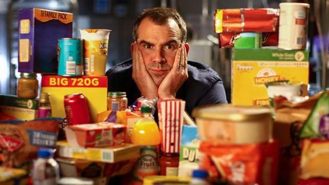 Dr Chris Van Tulleken sitting amongst a mountain of highly processed foods
