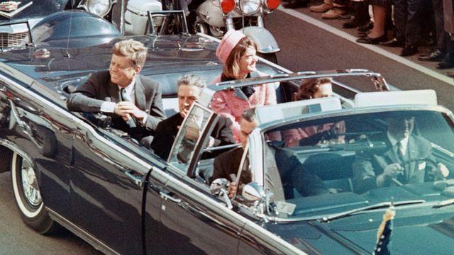 Kennedy y su esposa, Jacqueline, sonríen a al multitud desde un auto descapotado