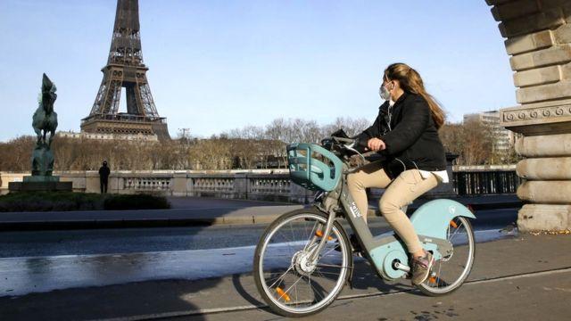 A woman rides a bike in Paris