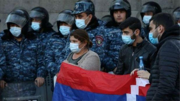متظاهرون يحملون العلم الوطني بينما يقف ضباط إنفاذ القانون أمام مبنى الجمعية الوطنية