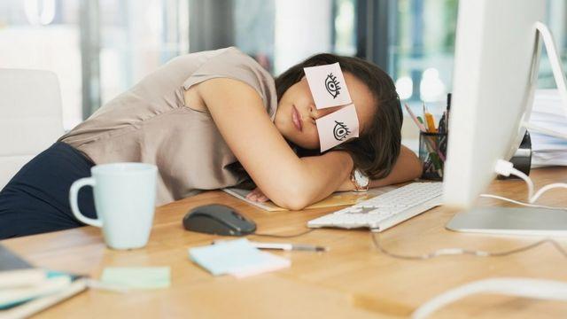 femme endormie au travail, la tête appuyée sur son bureau avec des affiches sur ses yeux, elle fait semblant d'être éveillée.