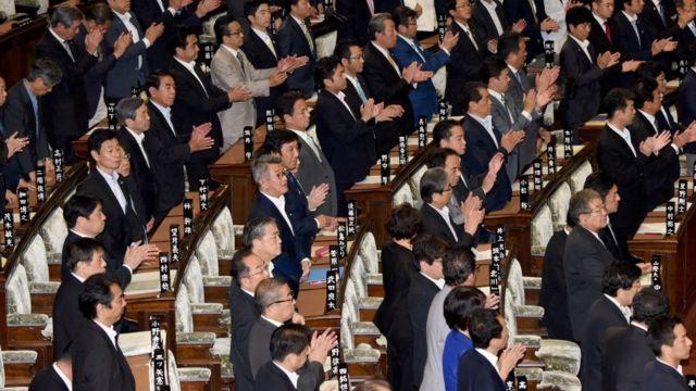 Membros do parlamento do Japão se levantam para apoiar um projeto de lei durante sessão plenária em Tóquio em 2 de junho de 2017