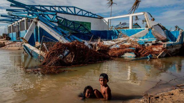 Crianças brincam em área alagada em meio a construção destruída por furacão na Nicarágua