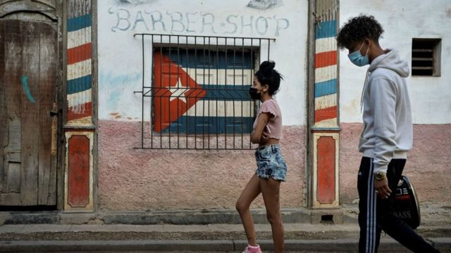 Two people walking on a Cuban street.