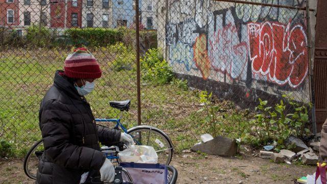 Mujer caminando en un barrio con grafiti en la pared de un terreno baldío en Estados Unidos