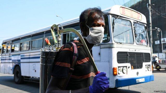 عامل يرش معقماً لتطهير محطة الحافلات
