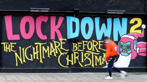 """رجل يمر بجوار لوحة جدارية كتب عليها: """"الإغلاق رقم 2 الكابوس قبل الكريسماس."""