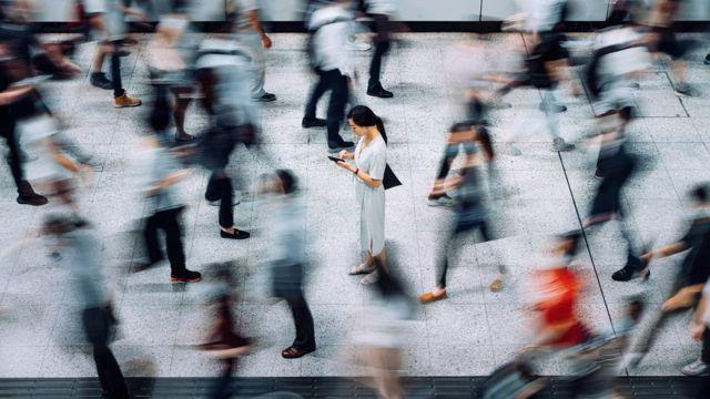 Une personne vérifie son téléphone au milieu de plusieurs personnes qui marchent.