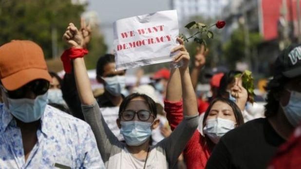 """متظاهرة ترفع لافتة كتب عليها """"نريد ديموقراطية"""""""