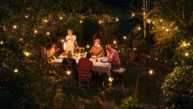 Friends talking and dining outside on a warm summers evening