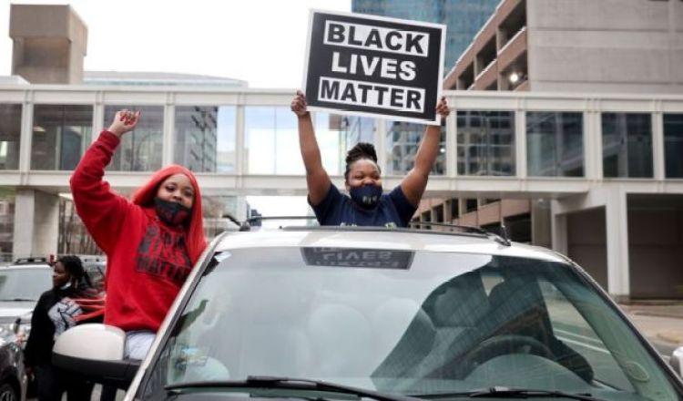 """Dos jóvenes levantan una pancarta que reza """"Black Lives Matter"""", tras conocerse el veredicto contra el exagente de policía Derek Chauvin."""