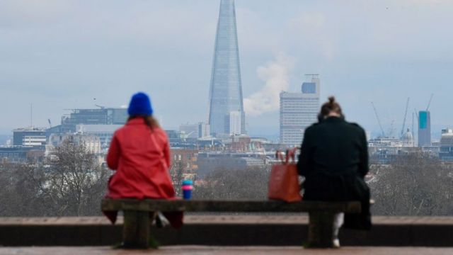 Two people sitting while embracing social distance between them in London, UK