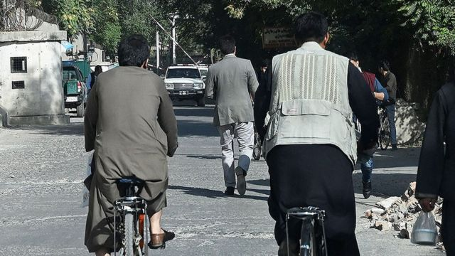 men with their backs walking in the street