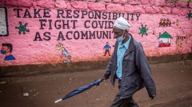 رجل يمر بجوار جدار مرتديا كمامة
