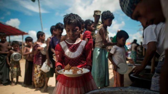 Sur cette photo prise le 1er octobre 2017, des réfugiés musulmans rohingyas font la queue pour recevoir de la nourriture dans une zone de distribution du camp de réfugiés de Balukhali près de la ville de Gumdhum à Cox's Bazar.