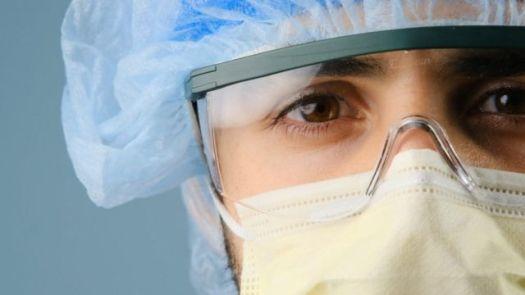 Enfermeira usando óculos, máscara e touca de proteção