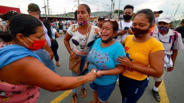 Mujeres lloran ante una cárcel de Ecuador tras la noticia de los amotinamientos
