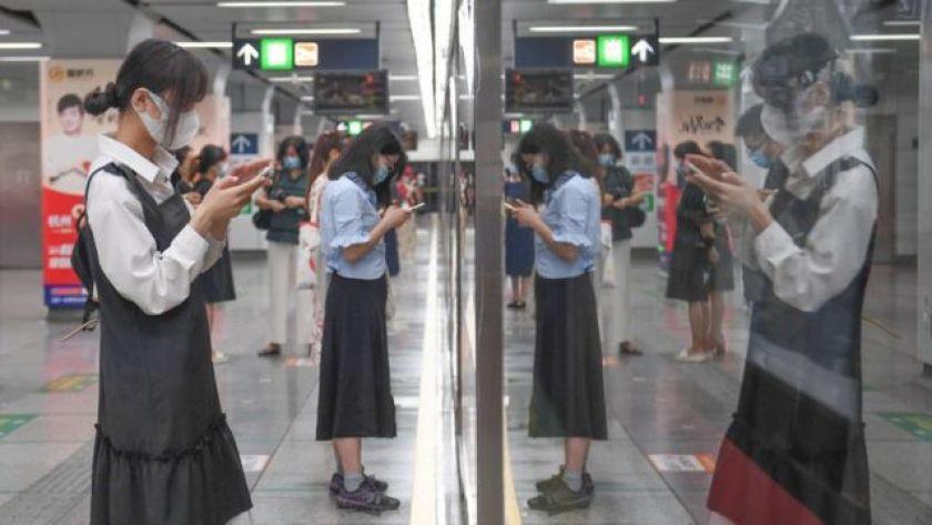 Passengers look at their smartphones while waiting for a subway train at a station, on April 27, 2021, in Hangzhou