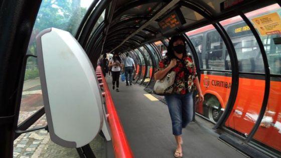 Pedestres com máscaras caminham na estação de metrô, com ônibus atrás, à luz do dia