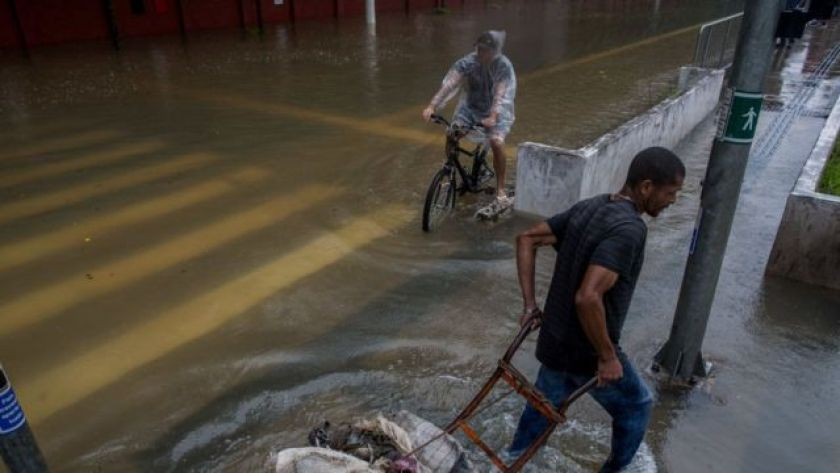 Young man pedals through flooding in São Paulo, while a man tries to transport a cart