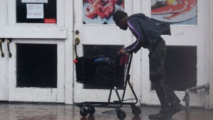 A man pushes a shopping trolley through the wind and rain in New Orleans