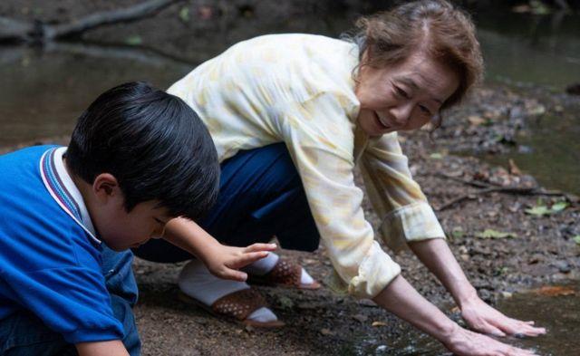 Una escena de Minari en donde aparecen plantando la tierra Soonja, el personaje de la abuela, junto a su pequeño nieto, David.