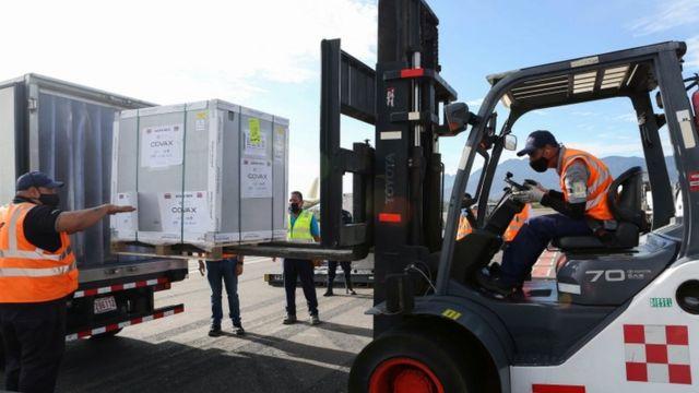 Trabajadores descargan un container con vacunas de AstraZeneca.