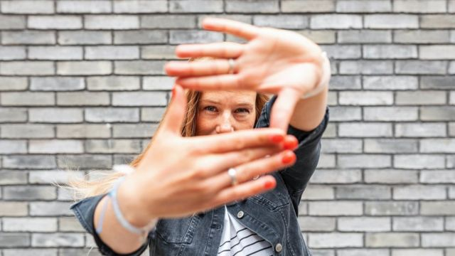 Close-up of woman against grey brick wall making finger frame sign