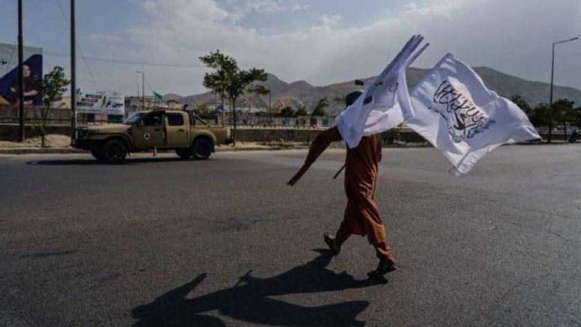 Boy selling Taliban flags in Kabul