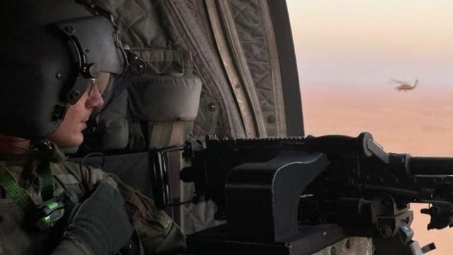 جندي أمريكي يحمل مدفع رشاش على متن طائرة هليكوبتر